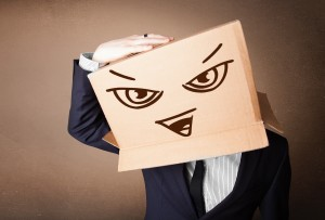 Businessman standing and gesturing with a cardboard box on his head with evil face